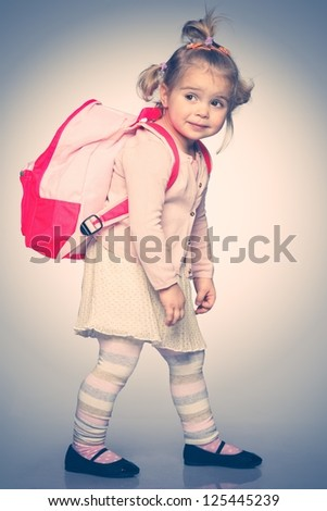 Funny little girl with backpack - stock photo