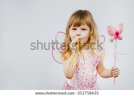 Funny little girl, with curly blond hair, wearing on pink dress and fairy wings, posing with magic stick and looking at camera, on white background, in studio, waist up
