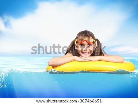 Funny little girl with diving glasses floating inflatable ring at sea, resort concept