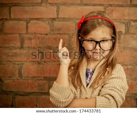 Funny little girl with glasses on brick wall background - stock photo