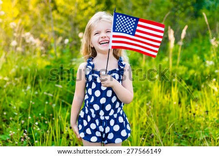 Funny little girl with long curly blond hair holding an american flag, waving it and laughing on sunny day in summer park. Independence Day, Flag Day concept