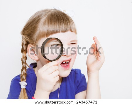 Funny little girl with loupe on white background - stock photo