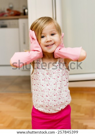 Funny little girl with rubber gloves at home. - stock photo