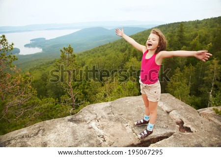 funny little  happy girl on the mountain top. children outdoors. inspiration - stock photo