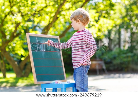 Funny little kid boy at blackboard practicing writing letters and mathematics, outdoor school or nursery. Kid learning and schoolboy concept. On summer sunny day. Back to school. - stock photo