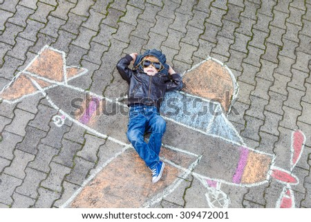 Funny little kid boy flying by a plane picture painting with colorful chalk. Creative leisure for children outdoors in summer. Family, happy childhood,  kids concept - stock photo