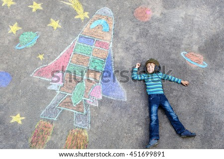 Funny little kid boy flying in universe by a space shuttle picture painting with colorful chalks. Creative leisure for children outdoors in summer. - stock photo
