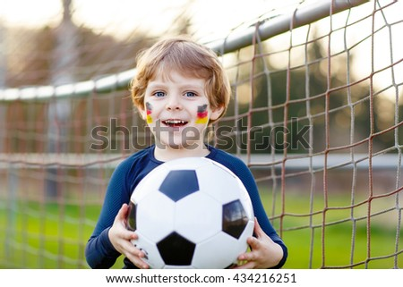 Funny little kid boy  having fun with playing soccer with football on field, outdoors. In white German national uniform and painted German flag on face. Happy child about european championship - stock photo