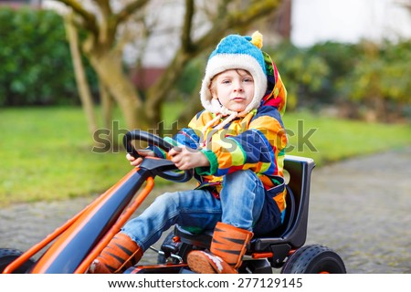 Funny little kid boy having fun with toy race cars, outdoors. Child driving car. Outdoor games for children concept. - stock photo