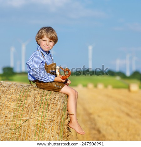 Funny little kid boy in traditional German bavarian clothes, leather shorts and check shirt, sitting on hay stack or bale and eating pretzel. Active outdoors leisure with children on warm summer day. - stock photo