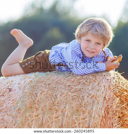 Funny little kid boy in traditional German bavarian clothes, leather shorts and check shirt, lying on hay stack or bale and dreaming. Active outdoors leisure with children on warm summer day. - stock photo