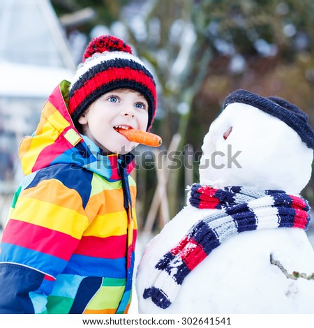 Funny little kid boy making a snowman and eating carrot, playing and having fun with snow, outdoors  on cold day. Active outdoors leisure with children in winter. - stock photo