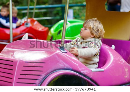 Funny little kid boy riding on car on roundabout carousel in amusement park. Happy toddler having fun outdoors on sunny day. - stock photo