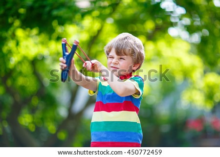 Funny little kid boy shooting wooden slingshot against green tree background. Child having fun in summer. On sunny warm day, active leisure for kids. - stock photo