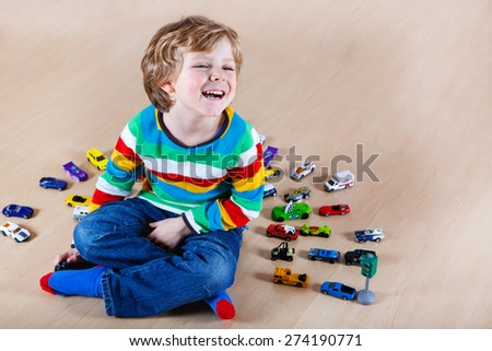 Funny little kid playing with lots of toy cars indoor. Child wearing colorful shirt and having fun. - stock photo