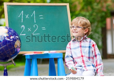 Funny little kid with glasses at blackboard practicing mathematics, outdoor. school or nursery. Back to school concept for little children - stock photo