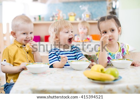 Funny little kid with open mouth eating in kindergarten group