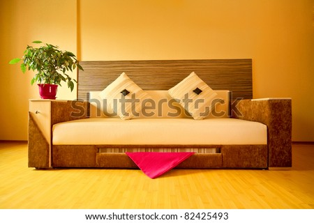 funny little man-couch with pillows in a bright yellow living room - stock photo