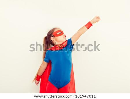 Funny little power super hero child (girl) in a blue raincoat. Superhero concept - stock photo