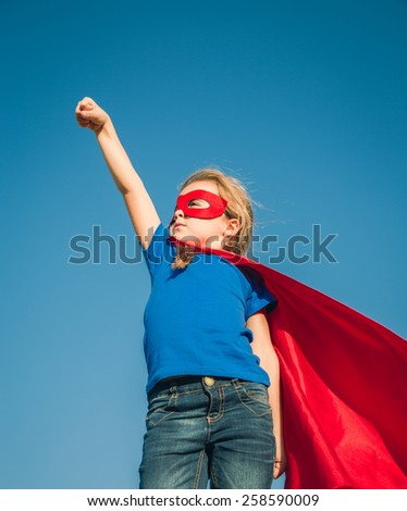 Funny little power super hero child (girl) in a red raincoat. Superhero concept.