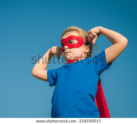 Funny little power super hero child (girl) in a red raincoat. Superhero concept. - stock photo