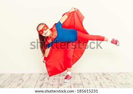 Funny little power super hero kid  (girl) in a blue raincoat. Superhero concept - stock photo