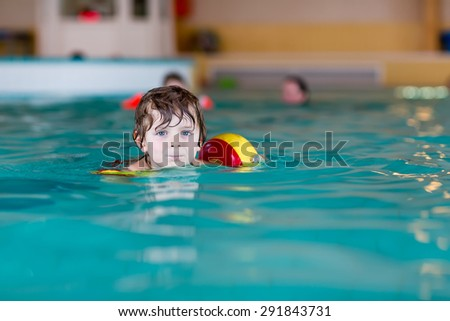 Funny little preschool boy with swimmies learning to swim in an indoor pool. Active and fit leisure for children. - stock photo