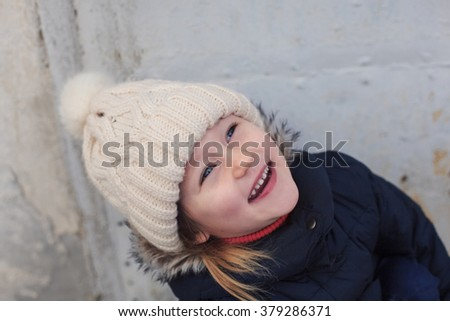 Funny little smiling girl in a white knitted hat and warm blue coat - stock photo