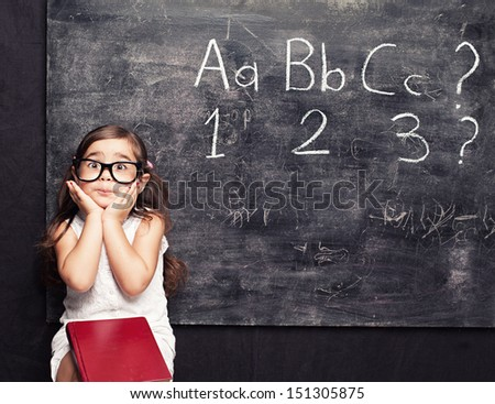 funny little squint eyed little girl posing sitting in front of blackboard