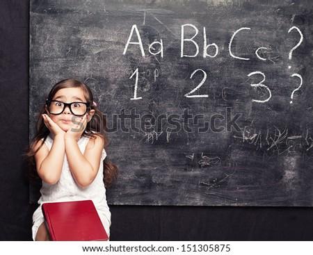 funny little squint eyed little girl posing sitting in front of blackboard - stock photo