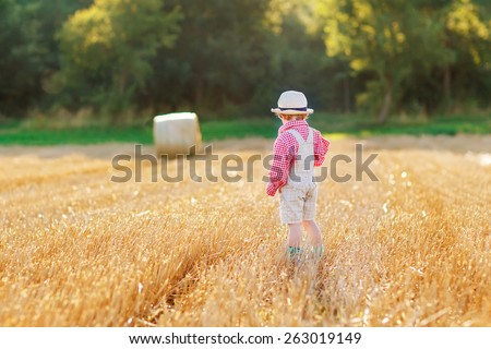 Funny little toddler boy in traditional German bavarian clothes, leather shorts and check shirt,  walking happily through wheat field near  hay stack or bale.  - stock photo