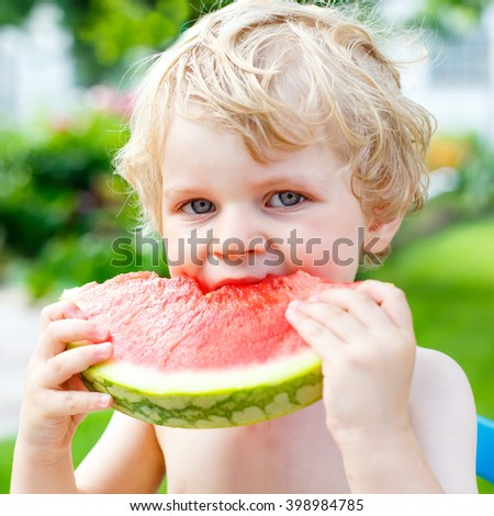 Funny little toddler boy with blond hairs eating watermelon at nursery outdoors. Kid tasting healthy snack. Healthy food for children. - stock photo