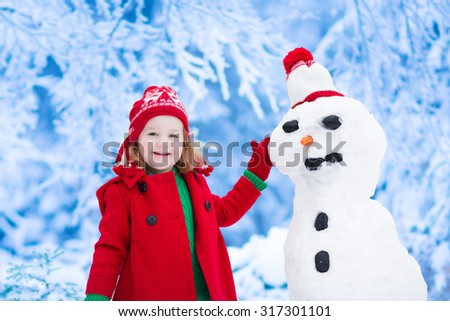 Funny little toddler girl in a red knitted Nordic hat and warm coat playing with a snow man. Kids play outdoors in winter forest. Children having fun at Christmas time. Child building snowman at Xmas - stock photo