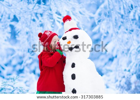 Funny little toddler girl in a red knitted Nordic hat and warm coat playing with a snow man. Kids play outdoors in winter. Children having fun at Christmas time. Child building snowman at Xmas - stock photo