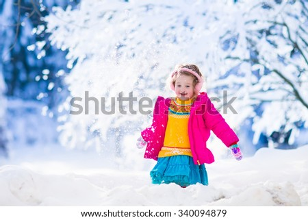 Funny little toddler girl playing snow ball fight. Kids play outdoors in winter. Children having fun at Christmas time. Child enjoying sunny day during Xmas vacation. - stock photo