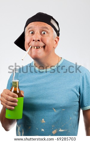 Funny looking middle age man with bad teeth holding a beer bottle and cigarette wearing a baseball cap. - stock photo