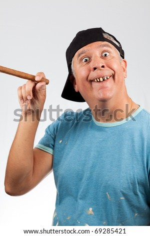 Funny looking middle age man with bad teeth holding a large cigar and wearing a baseball cap. - stock photo