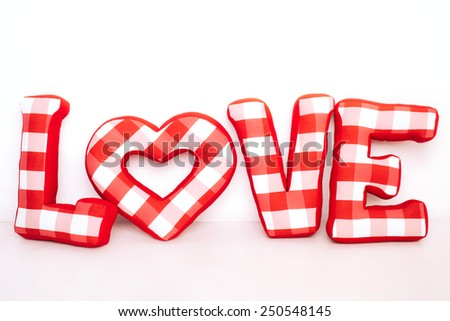 Funny love word of plush red letters on white background. Full plaid textile. February 14, Valentine's Day concept shot with text space. Top view. High resolution - stock photo