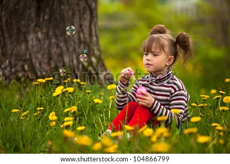 Funny lovely little five-year girl blowing soap bubbles in the park