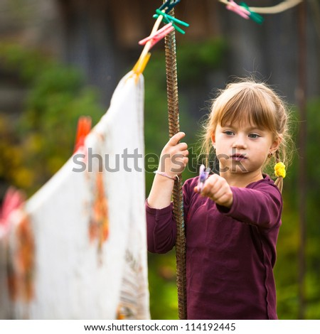 Funny lovely little five-year girl with clothespin outdoor - stock photo