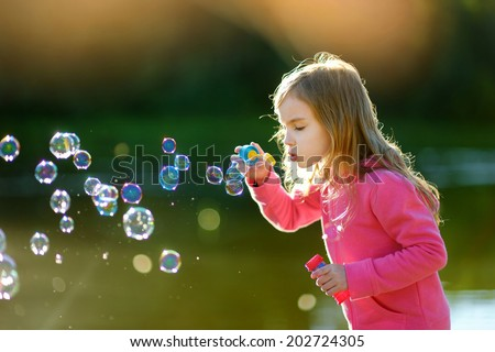 Funny lovely little girl blowing soap bubbles on a sunset outd?ors - stock photo