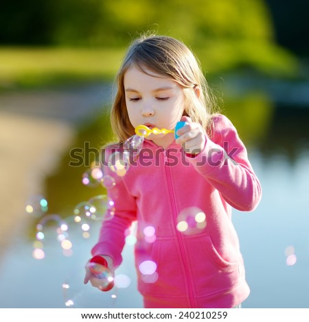 Funny lovely little girl blowing soap bubbles on a sunset outdoors - stock photo