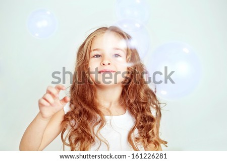 Funny lovely little girl in white dress playing with soap bubbles - stock photo