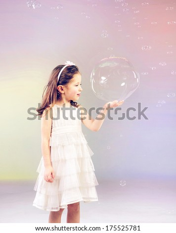 Funny lovely little girl playing with soap bubbles - stock photo