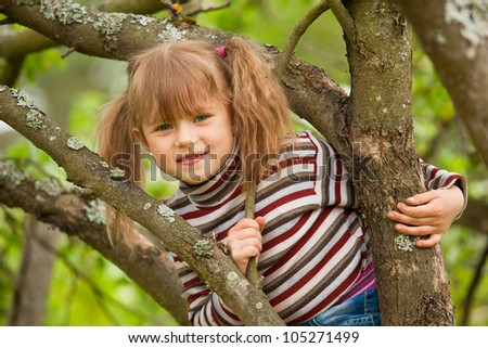 Funny lovely little girl posing sitting on a tree in the garden - stock photo