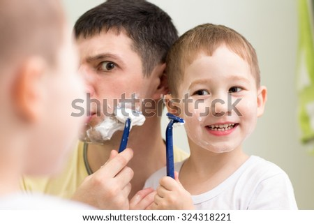 Funny man and his son little child shave looking at mirror in bathroom - stock photo