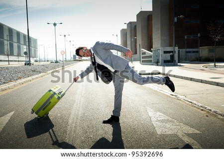 Funny man dressed in suit with a suitcase - stock photo