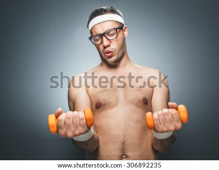 Funny man exercising and doing fitness. Nerd athletic man using small dumbbells for bodybuilding. Dark gray background. Studio shot - stock photo