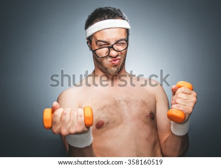 Funny man exercising and doing fitness. Nerd man using small dumbbells for bodybuilding. Dark gray background. Studio shot - stock photo