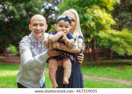 Funny man hugs from behind woman with dreamy little girl